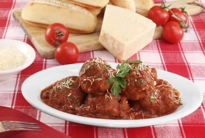 Italian meatballs in an oval dish.