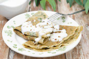 crepes with spinach with yogurt sauce and nuts on a plate