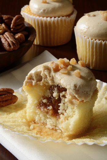 A caramel apple cupcake with pecans with a bite out of it