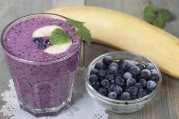 Smoothies of frozen blueberries and banana with yogurt. Blueberries and strawberries in a white cups and a banana in the background on a wooden table.