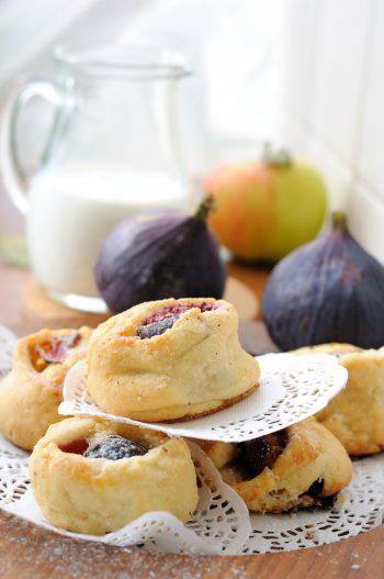 A little pile of fig cookies on a wooden plate.
