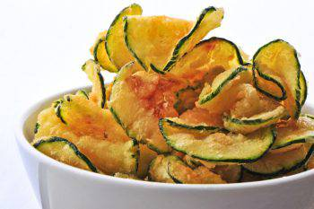a modern take on potato chips, these are deep fried zucchini chips (eaten warm and salted, yum) in a white bowl on a white background, popular as a bar snack.
