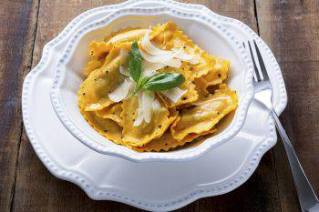 Butternut squash mezzaluna ravioli or tortellini in a bowl on rustic wood