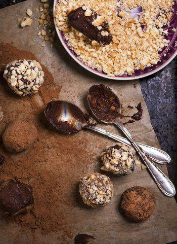 Assorted dark chocolate truffles with cocoa powder, biscuit and chopped hazelnuts over baking paper, selective focus