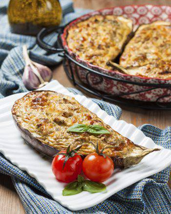 hot baked eggplant stuffed with cheese, cottage cheese, fresh herbs on a white plate on a wooden table