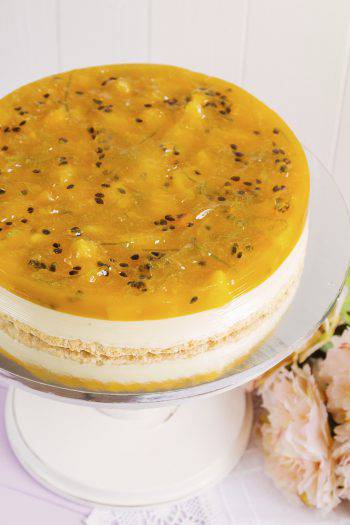 Fresh fruit cake decorated with passionfruit and oranges mousse on light background. Modern european cake. Shallow focus