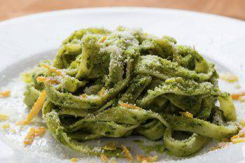 fresh green vegetarian tagliatelle dish on white plate on wooden table