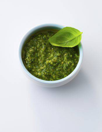 Homemade pesto in bowl with basil leaf