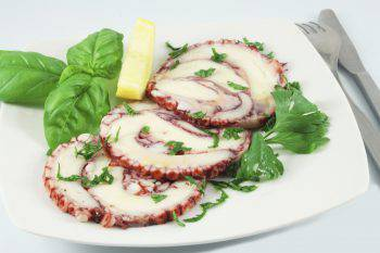 A dish of octopus carpaccio with basil and a lemon slice