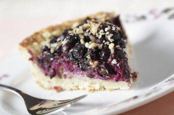 Close-up of a slice of blueberry pie on a white plate