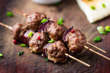 Meat kebab, beef balls on skewer with onions, sauce guacamole